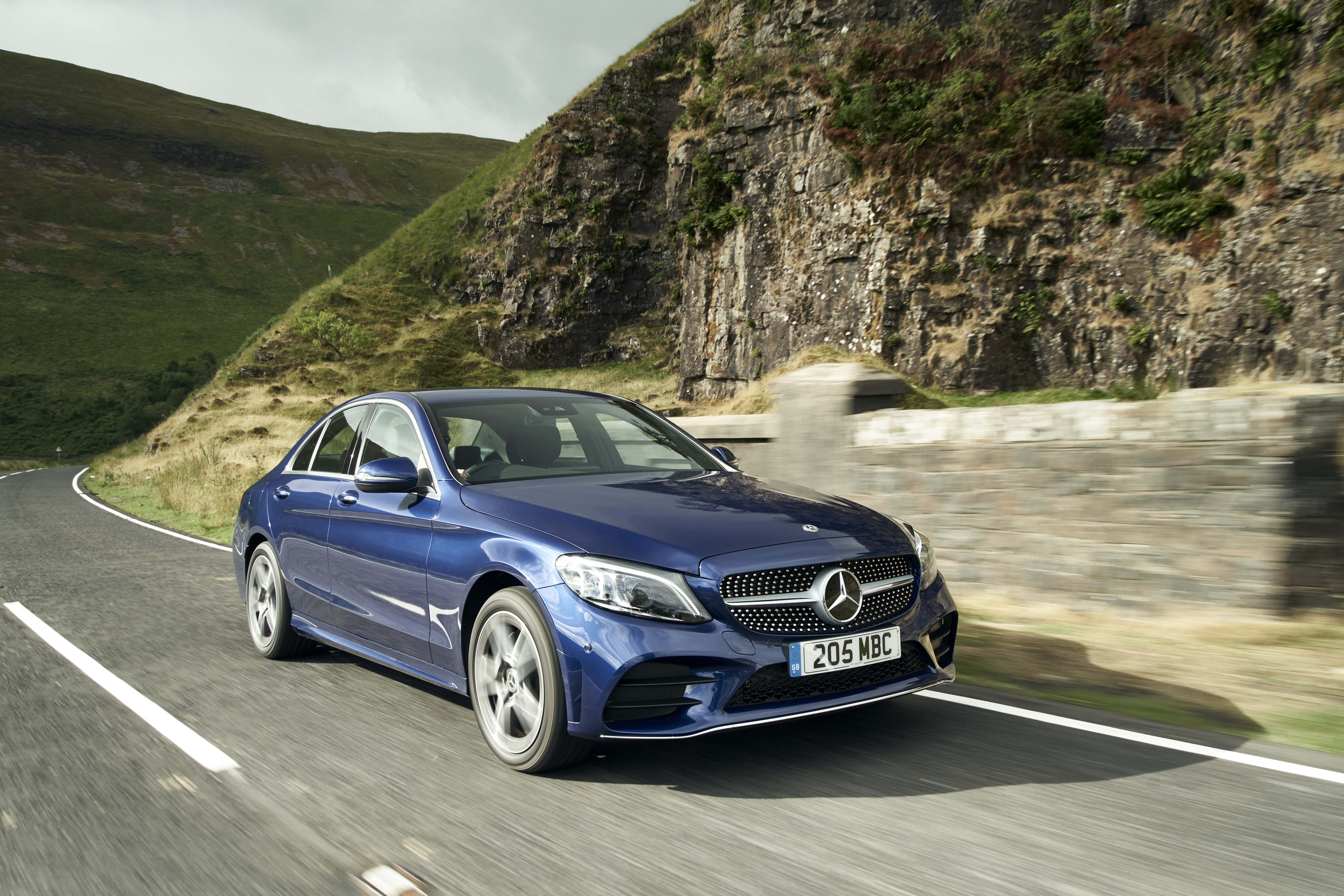 Blue Mercedes-Benz C-Class driving around a corner