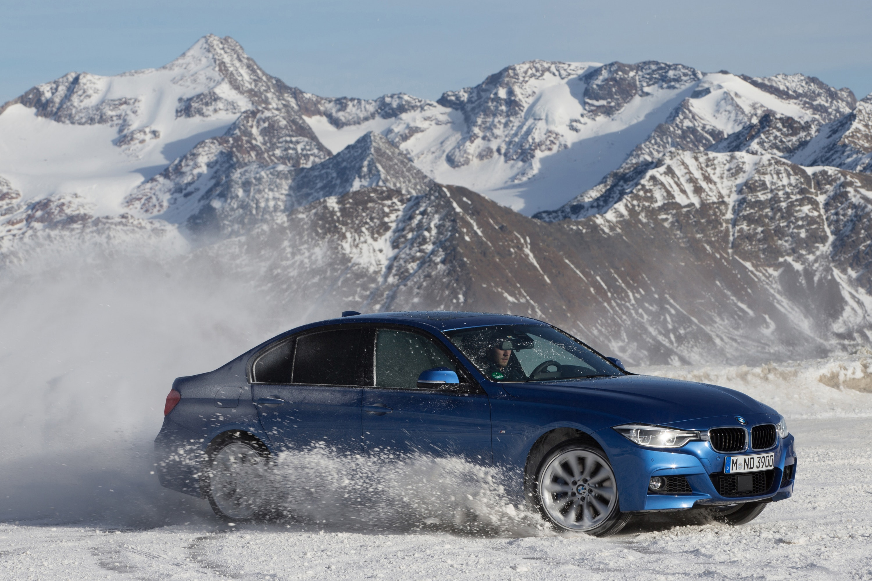 Blue BMW driving in snow