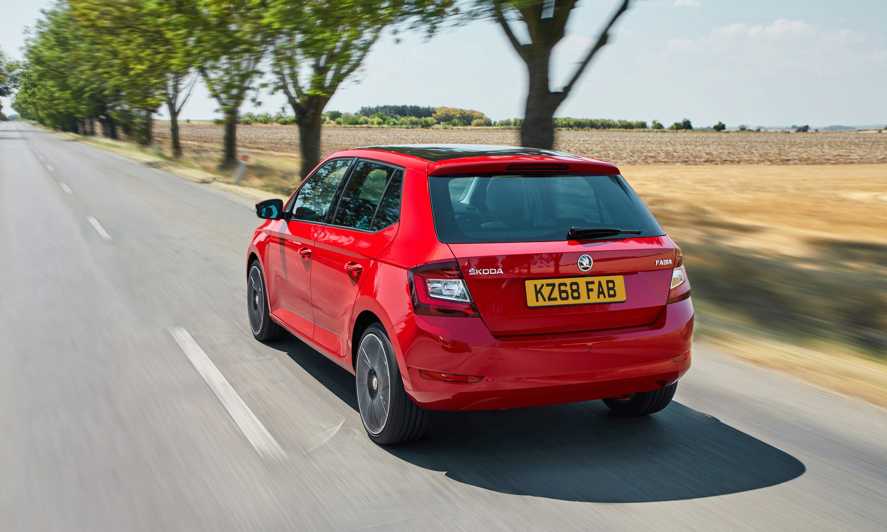 Rear view of a red Skoda Fabia driving on a road