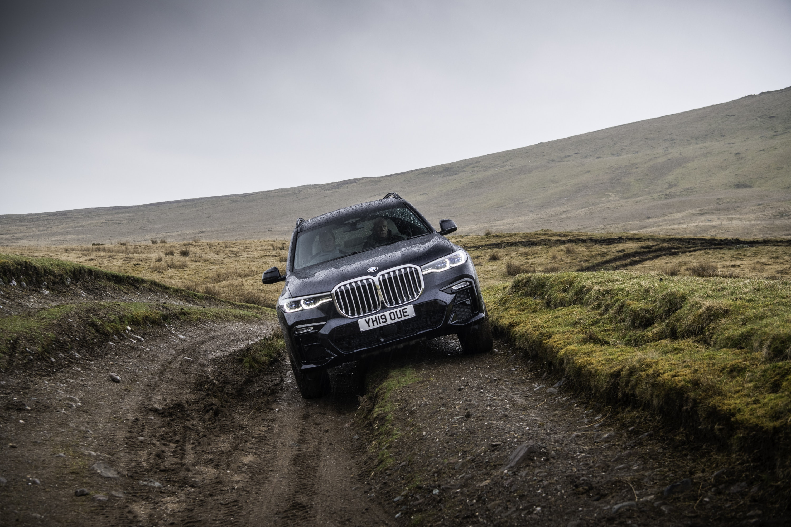 front view of the BMW X7 driving on a muddy trail