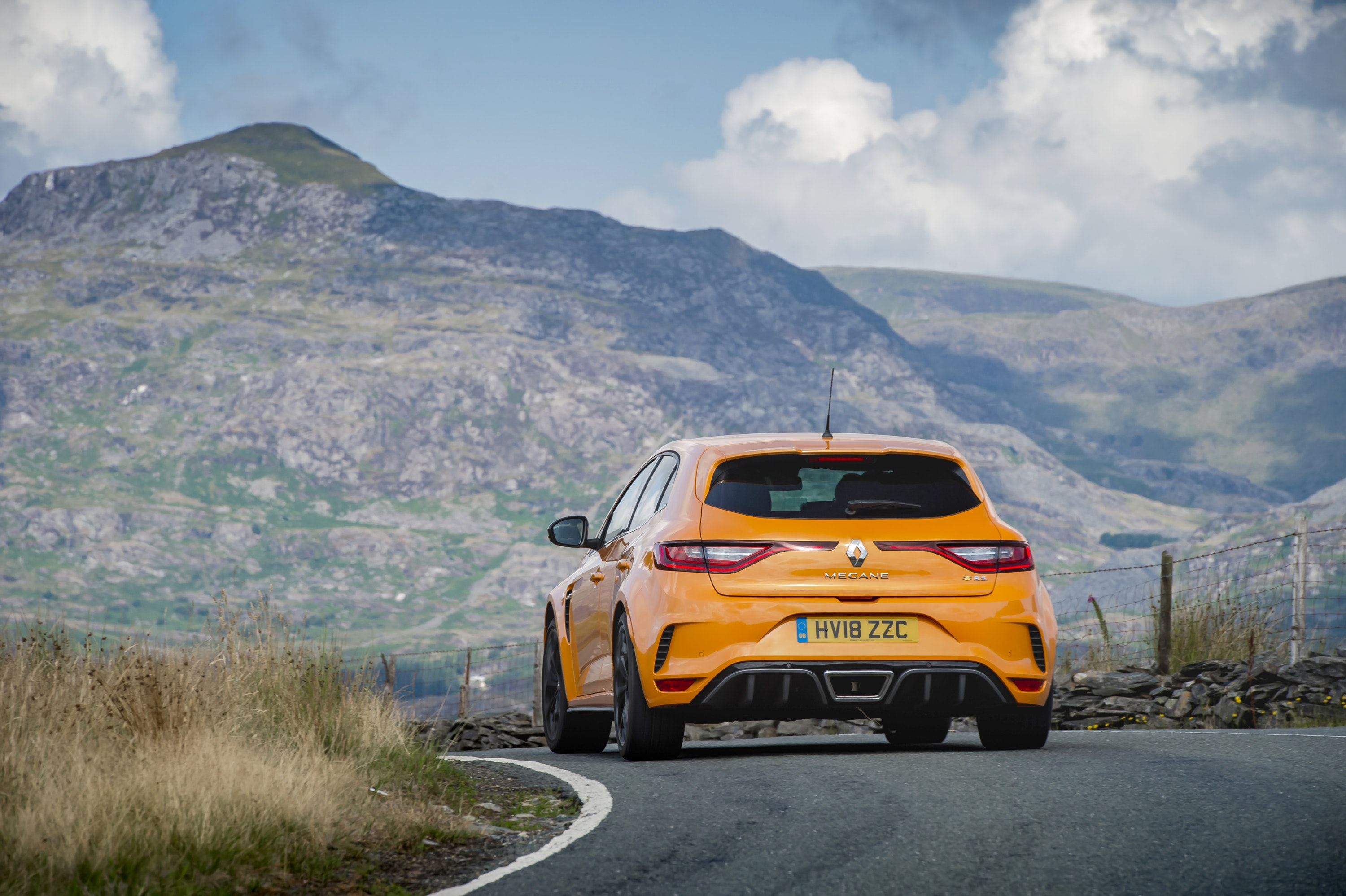 rear view of a Orange Renault Megane RS parked on a road with a mountain in the background