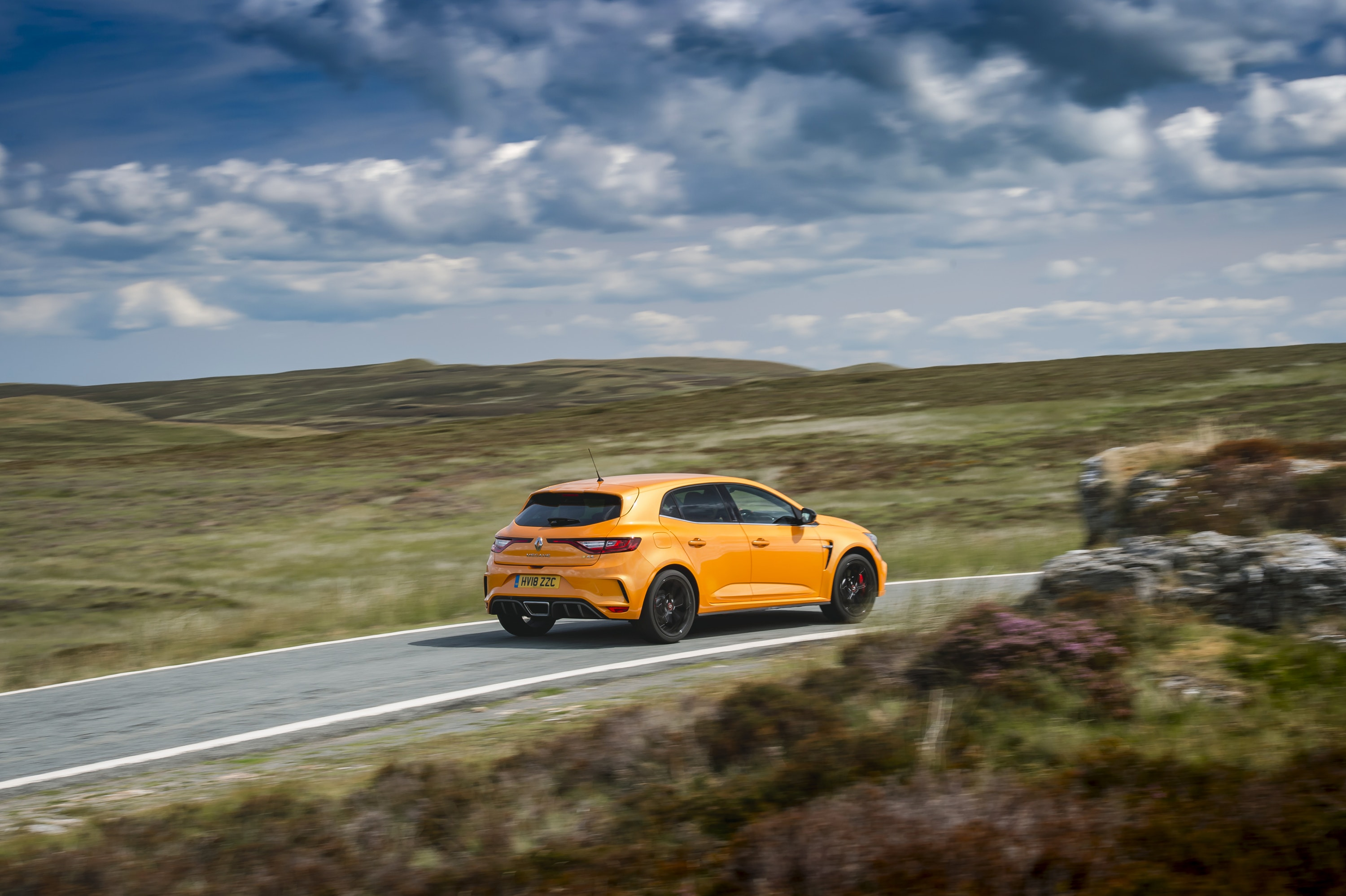 rear view of a orange Renault Megane RS driving on a road