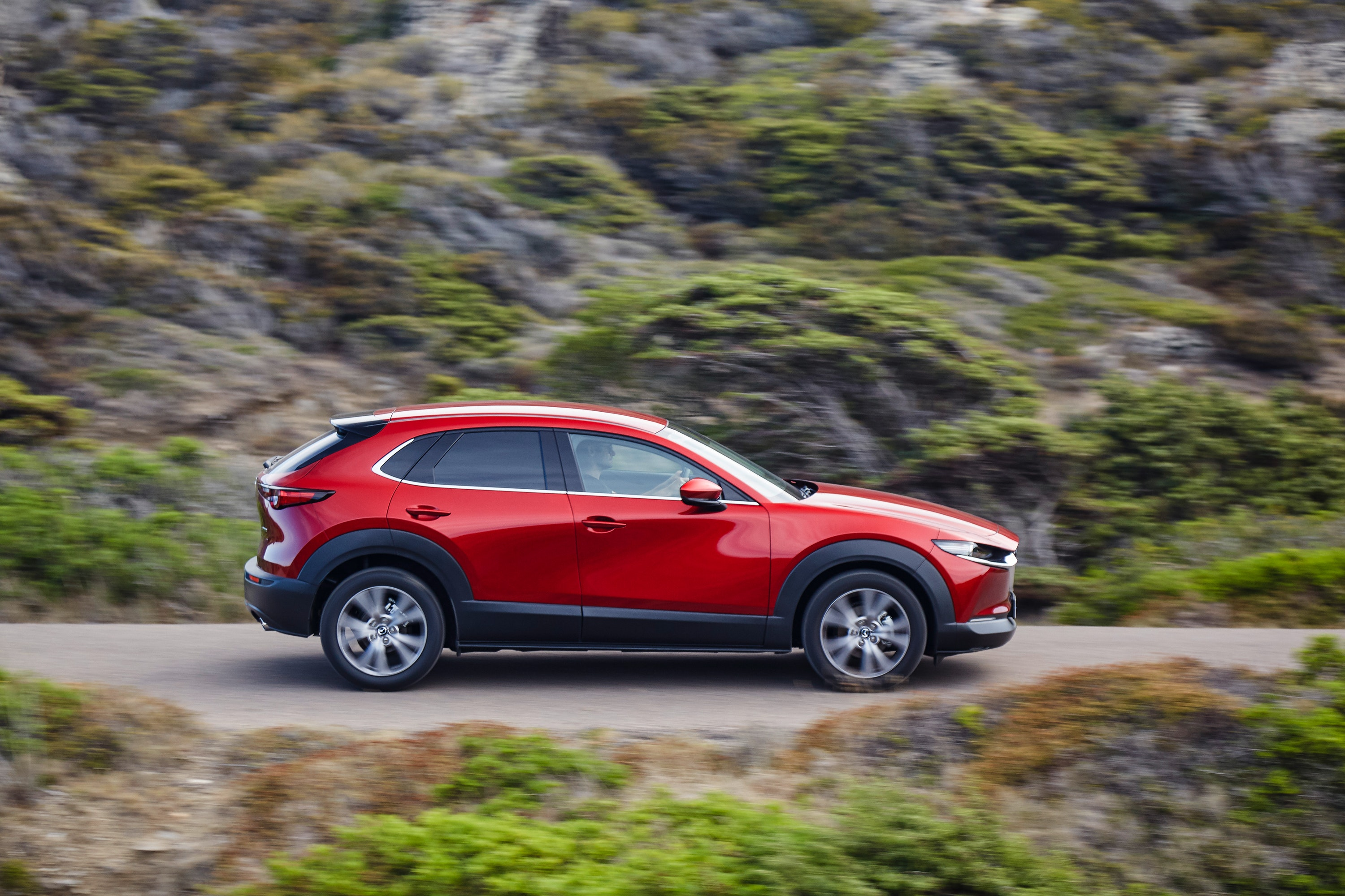 Side view of Mazda CX-30 driving on a road